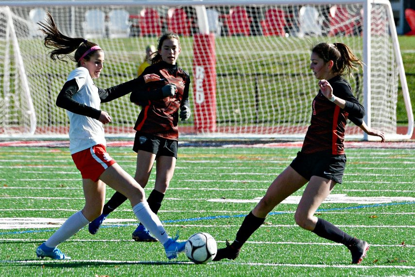 Mohonasen's Izzy O'Clair, right, and Jamesville-Dewitt's Grace Dimkopoulos both kick at the ball during Saturday's game.