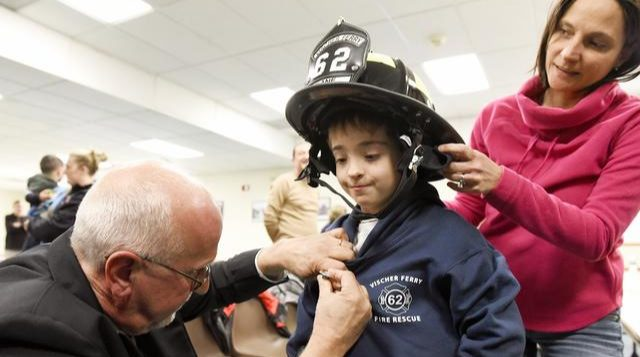 Vischer Ferry Fire Co. President George Donohue pins honorary member Patrick Kane with his badge as his mother watches.
