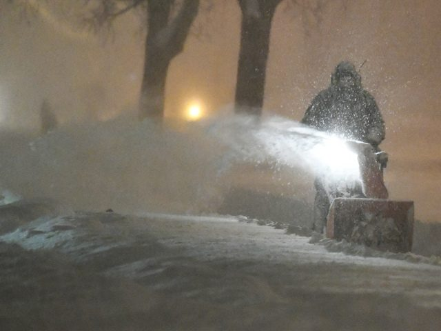 A bundled-up person operates a snowblower at the intersection of Union Street and Maryland Avenue late Sunday evening.
