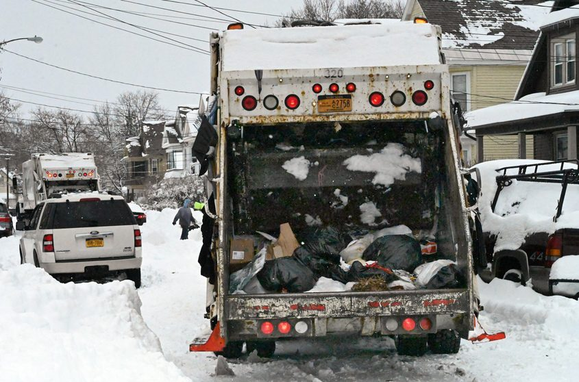 A Schenectady garbage truck is held up because of parked cars.