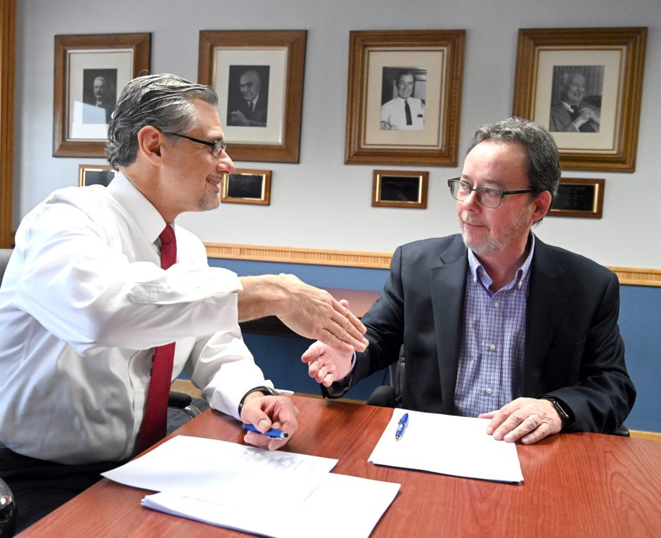 Gazette Publisher John DeAugustine, left, and Recorder Publisher Kevin McClary shake at the contract signing on Monday.