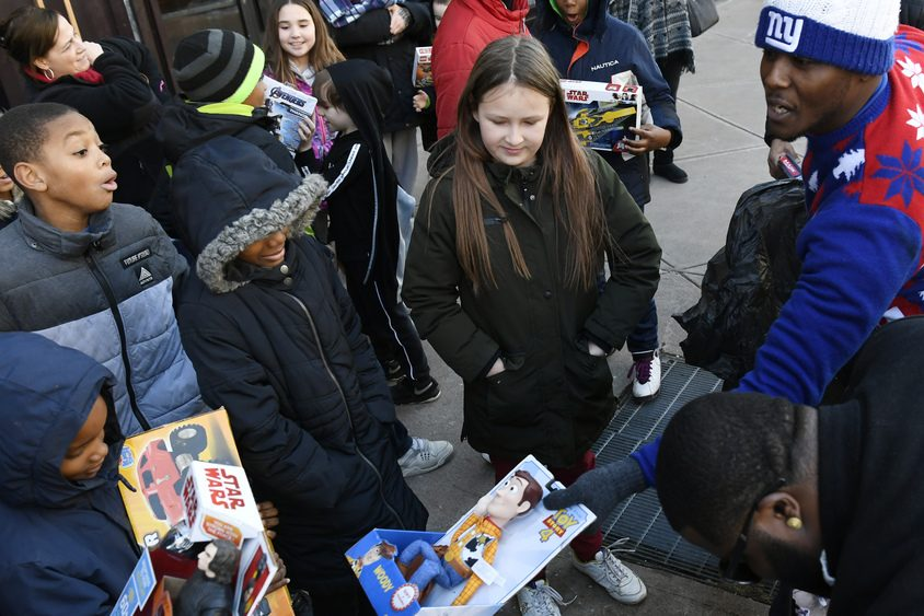 DJ Ketchup hands out toys in front of Proctors during the 5th annual Random Santa Drop Off on Tuesday.