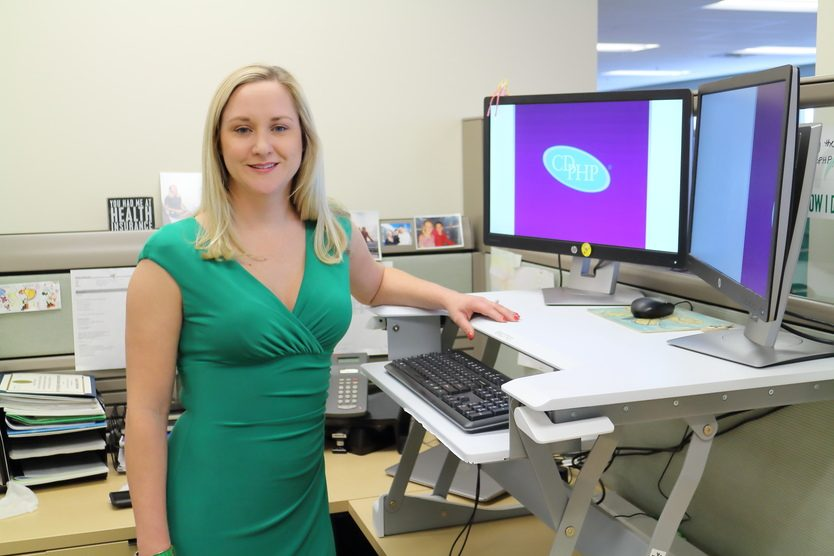 Ali Skinner, vice president of communications strategy for CDPHP, is shown at her stand-up desk.