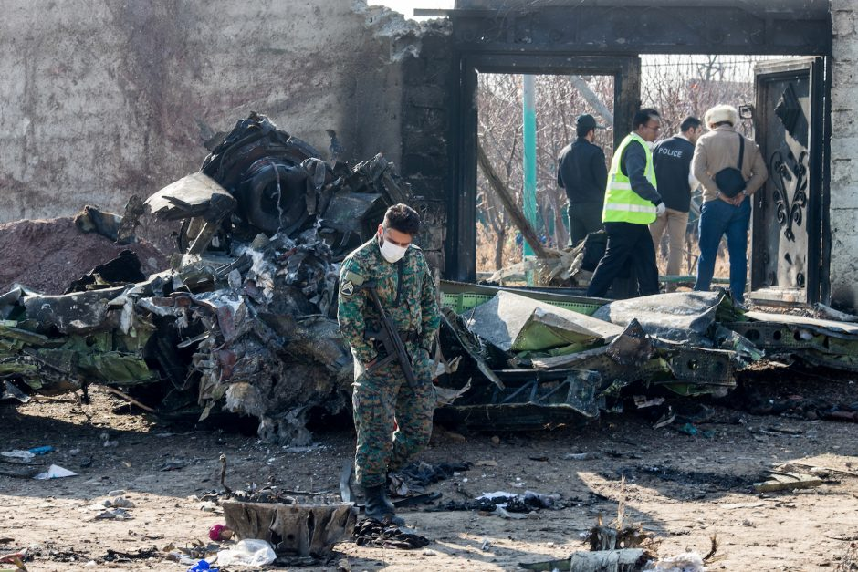A security official examines debris at the site of the Ukraine International Airlines crash on Jan. 8, 2020.