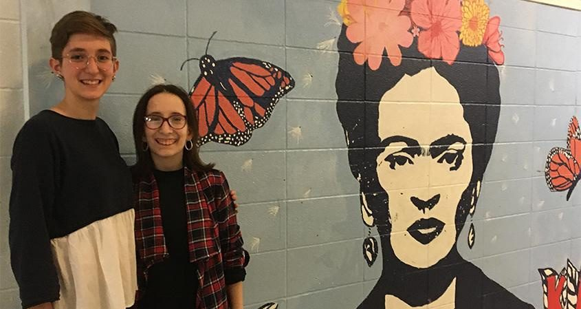 Emma Lindenfelser, left, and Isabella Smarro pose next to a mural at Schenectady High School last week.