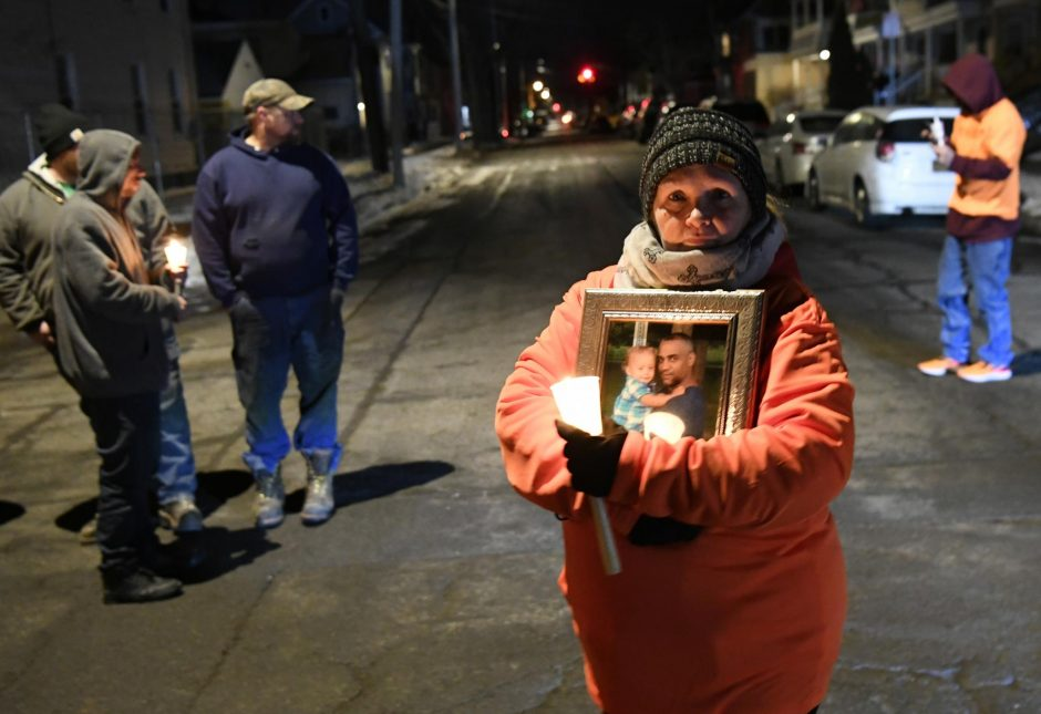 Nancy Kelly stands in the intersection of Linden and Becker streets at 1 a.m. for a candle light vigil for Roscoe Foster.