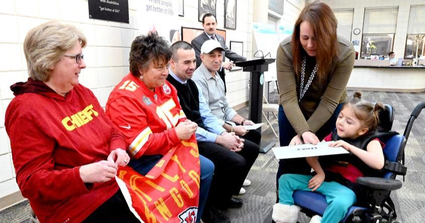 Sadie Dutcher, 7, of the Center for Disability Services in Albany, and teacher Blair Murray distribute Super Bowl tickets.