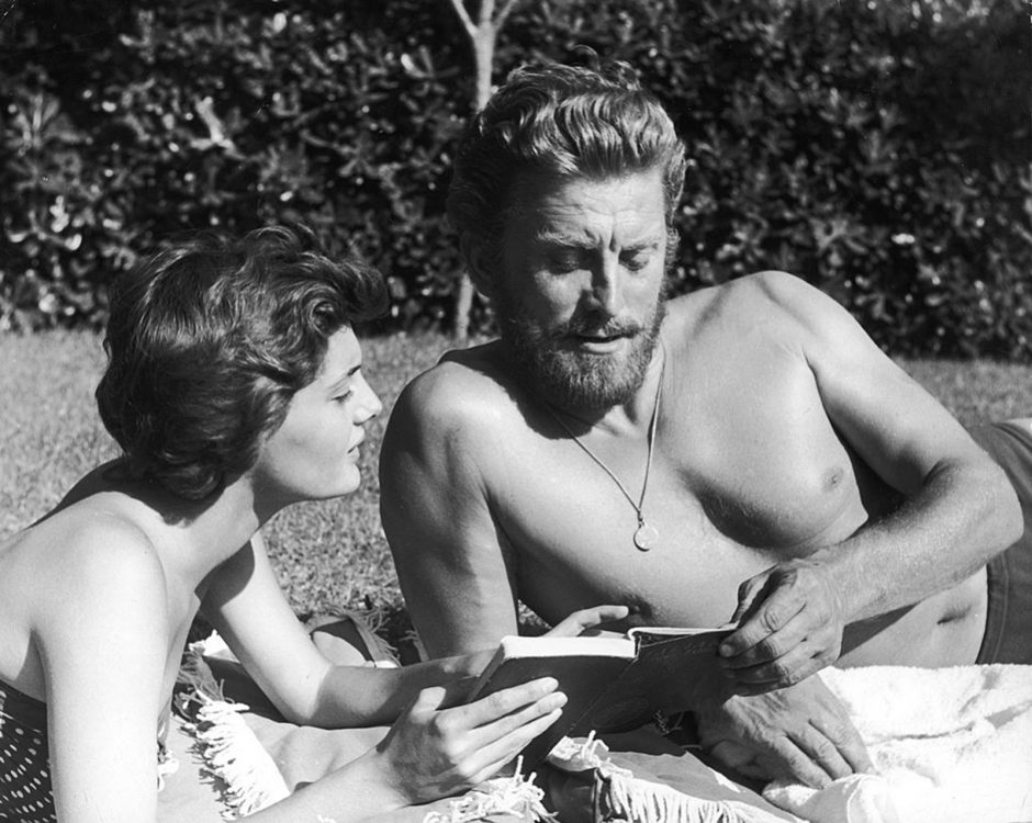 Actor Kirk Douglas looks at a book with his second wife, Anne Buydens, in 1956.