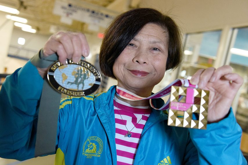 Lichu Sloan shows off a medal for having run marathons on all seven continents and in her 100th country, Croatia.