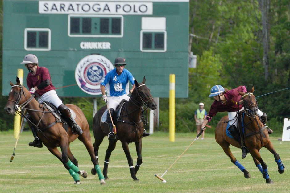 Saratoga Saddlery's Lindsey Vance reaches for the ball against HL Polo during their match at Saratoga Polo in Greenfield Center.
