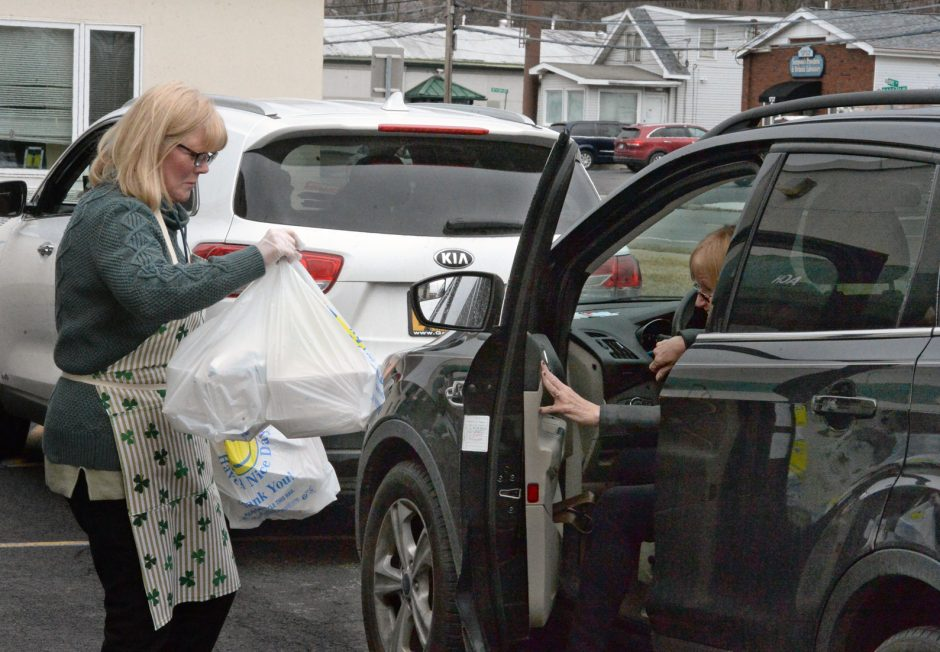 Michol Murphy brings dinner to a customer in the drive-up lane at the Hibernians building on Tuesday..