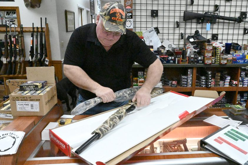 Salesman Rob Paige of Target Sports on Route 50 in Glenville on Tuesday prepares a shotgun for delivery.