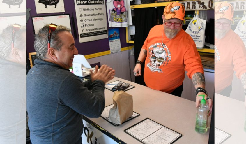 Robert Canton, right, part owner Memphis BBQ on Van Vranken Avenue, Schenectady, offers customer Richard Holmes hand sanitizer.