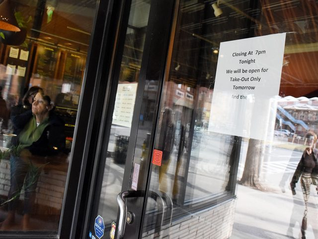 A sign announcing a change in operating hours is posted at Uncommon Grounds on Broadway in Saratoga Springs on March 16.