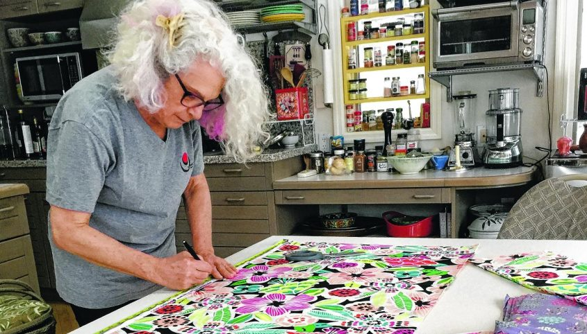 Ginger Ertz cuts fabric into mask-size rectangles in her kitchen.