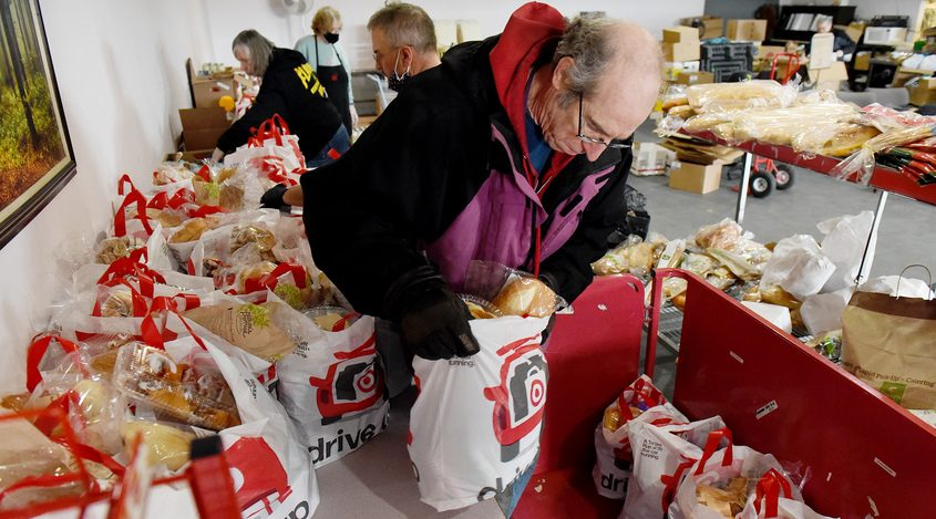 Volunteer Craig Lange, of Scotia, moves filled bags with a weeks worth of food on a cart during the weekly pickups