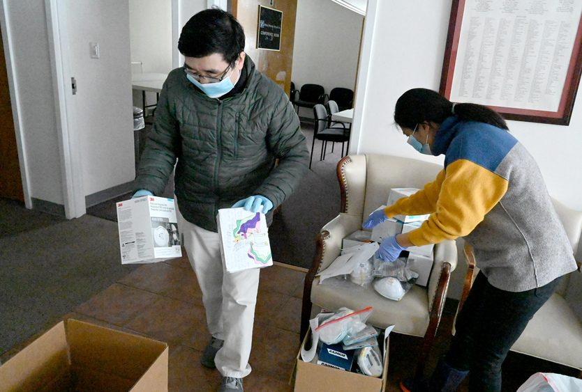 Yifeng Wang, left, and Li Zhang pack boxes of masks at the Chinese Community Center to send to area hospitals.