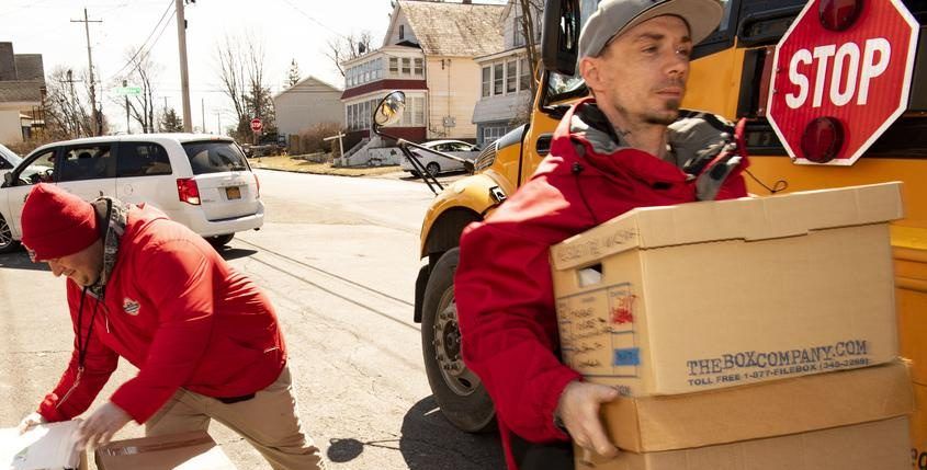 Schenectady City Mission clients Jason Caldwell and Sean Willi load boxes of food onto a school bus Thursday.
