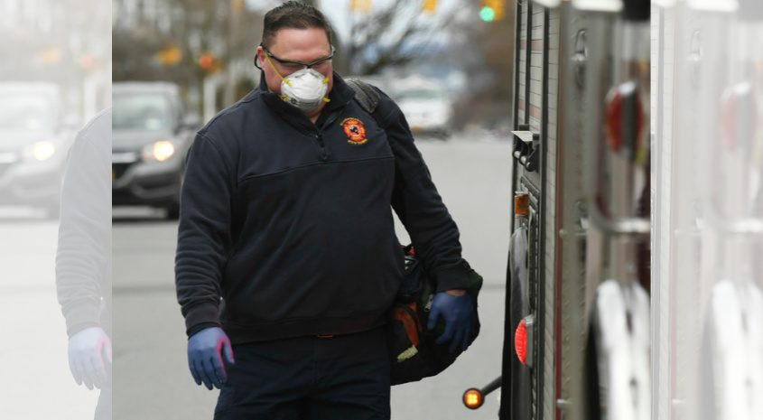 Suited up for Covid-19 precautions, Schenectady firefighter Randy Pierre carries gear answering a medical call Tuesday