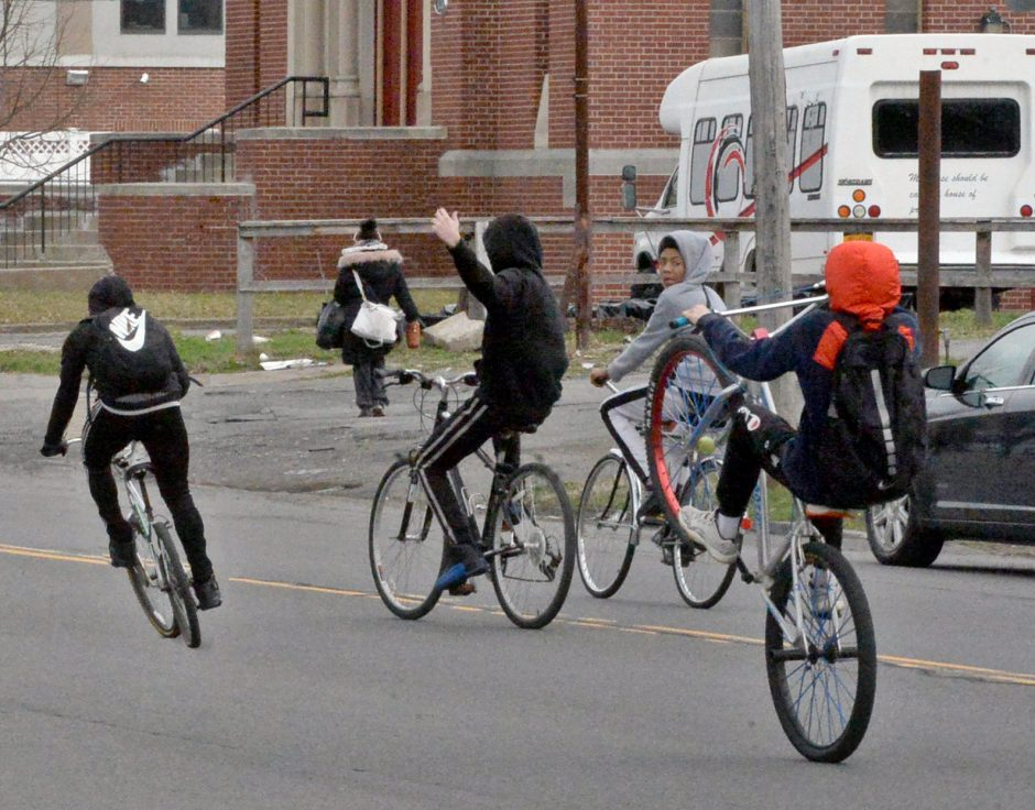 A group of children on bicycles, partially pictured, heads up State Street in the middle of the road Sunday.nday