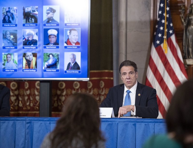 With photos of some of the dead behind him, Gov. Andrew Cuomo gives his daily COVID-19 briefing Wednesday.