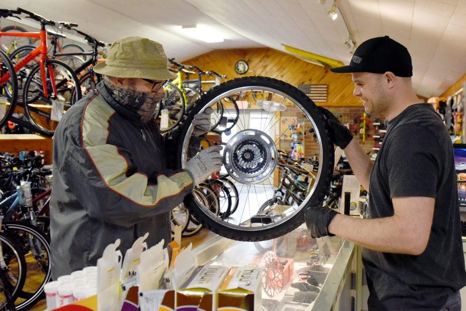 Luis Soto, of Gloversville, brings in a wheel to get repaired by employee Joe Trimarchi at The Bike Works in Johnstown.