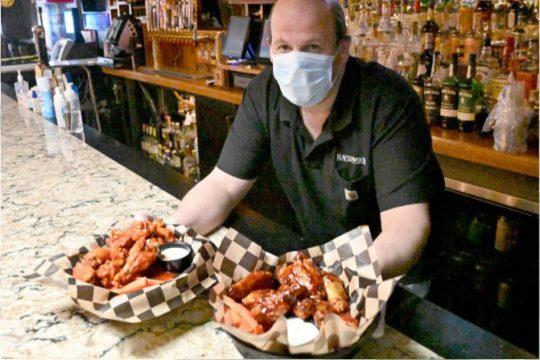 Ravenswood Pub owner Scott Schreifels  shows two dozen chicken wings at his pub on Wednesday.