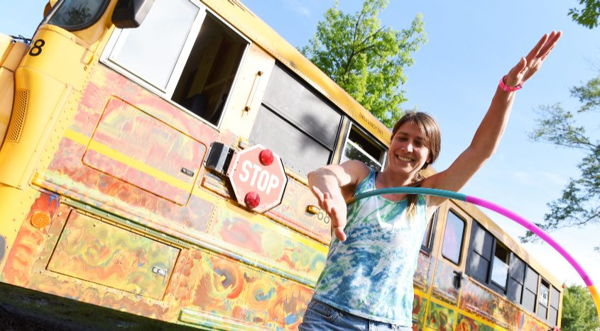 A Dead & Company fan Hula-Hoops in front of a bus at Lee's Park Campground in Saratoga Springs before the band's concert on June