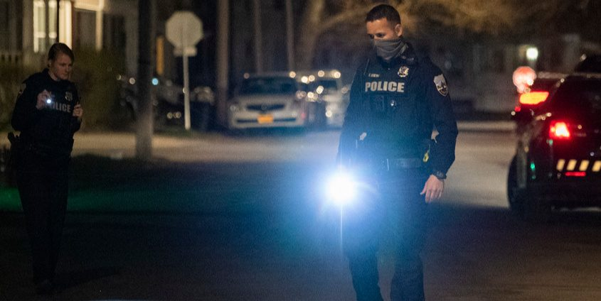 Officers look for shell casings on McClyman Street after a shots fired incident late Wednesday