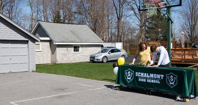 Schalmont basketball's Shane O'Dell signs a letter of intent to play at The College of Saint Rose in his driveway Tuesday.