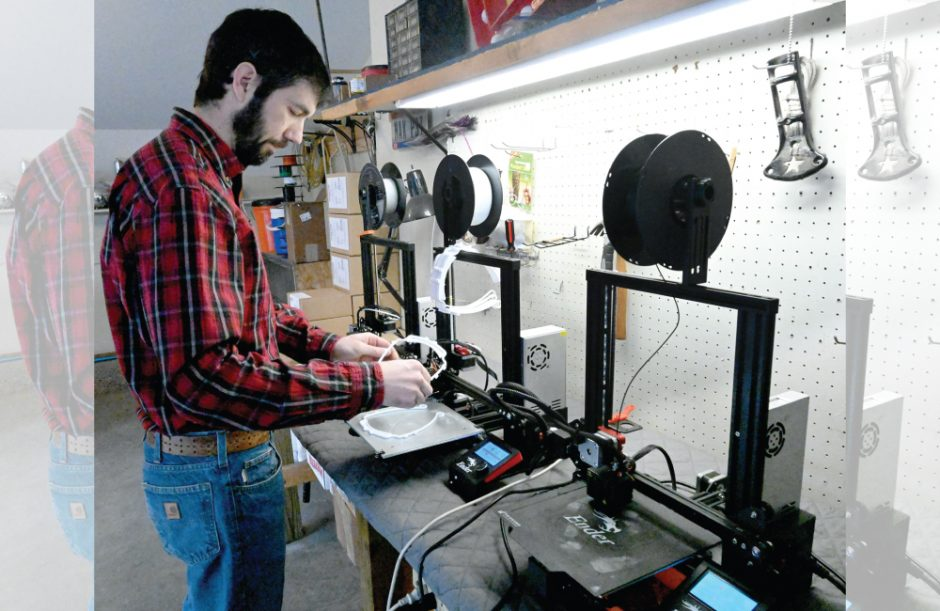 Max Corbett checks on the 3D printing process for the Northeast Face Shield Project at his home in Altamont.
