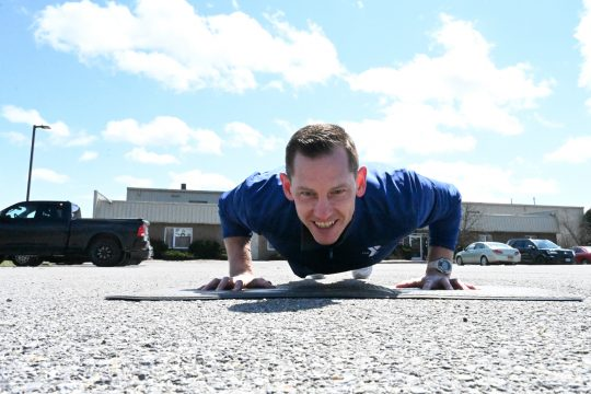 Chris Defibaugh, CEO of the Johnstown YMCA, exercises in the parking lot during a Facebook workout.