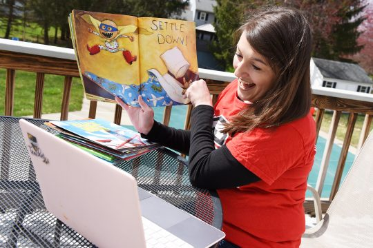 Beth Trela reads a children's book while connecting with students via her computer on April 15.