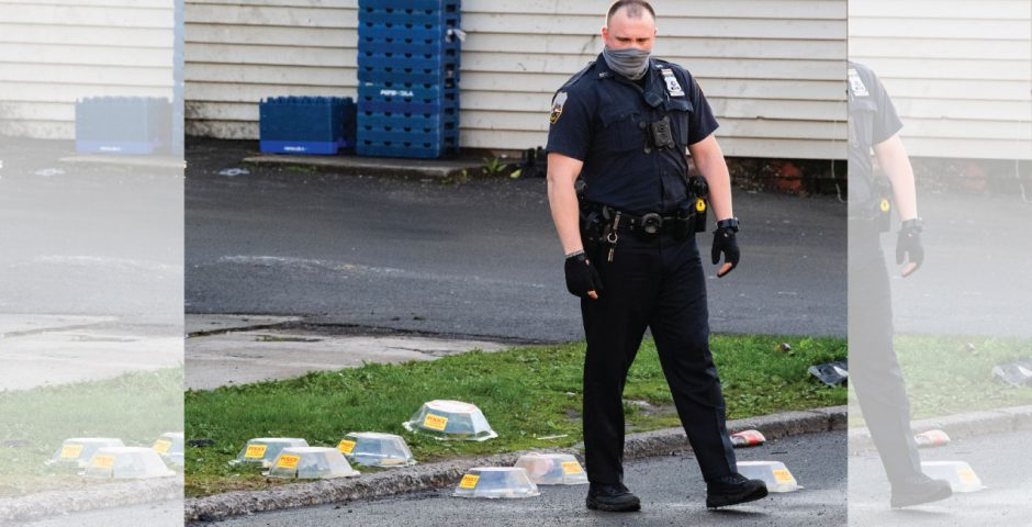 Officer Steven Flood steps in between evidence markers covering shell casings after a shooting Friday.