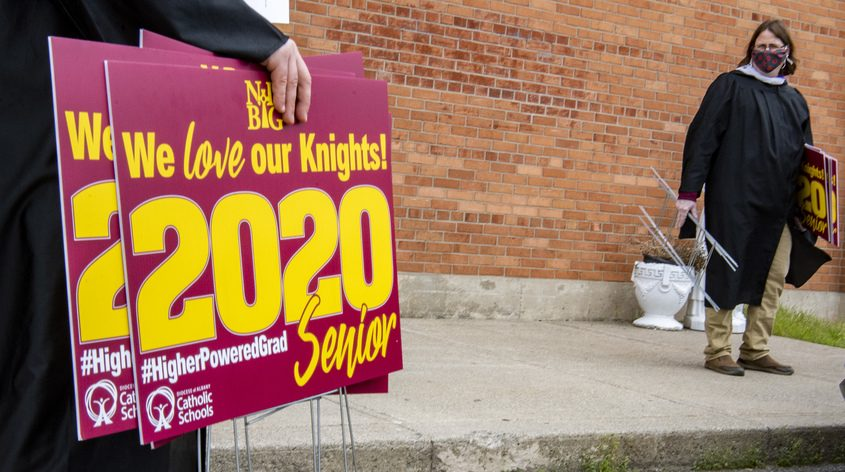 Notre Dame-Bishop Gibbons art teachers grab signs to put on the front lawn of seniors who are graduating in June Wednesday
