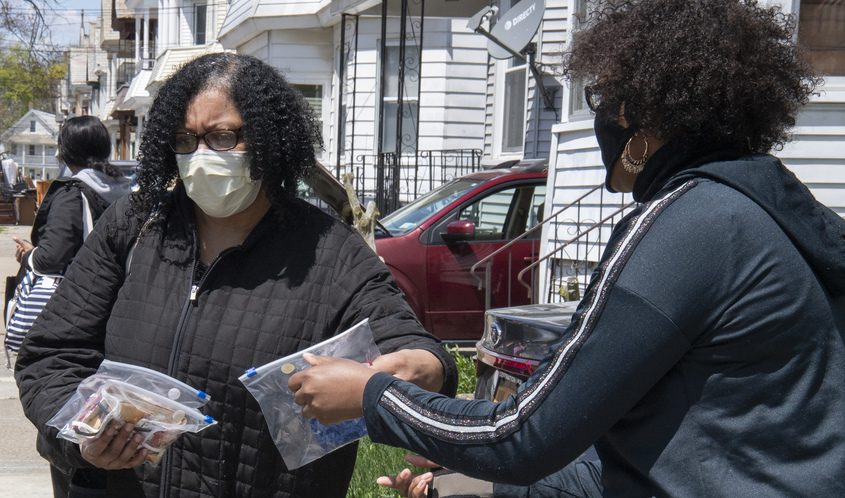 Thearse McCalmon, right, hands out masks in front of C.O.C.O.A. House on Stanley Street in Schenectady Thursday