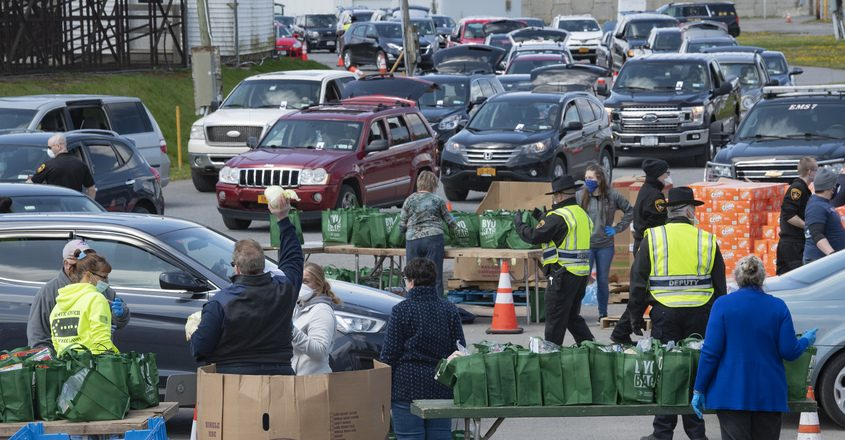 Cars line up 3 lanes wide at the Fonda Fairgrounds for a drive-through Food Bank Friday