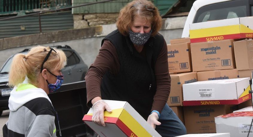 Kathy Yurkewecz unloads a case of rains off a pick-up truck, handing to Seana Modoski Friday at the Amen Place Soup Kitchen.