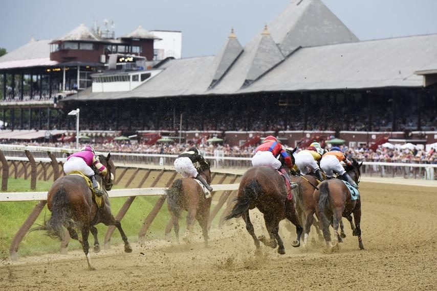 Horses run around the grandstand turn at Saratoga Race Course in this file photo