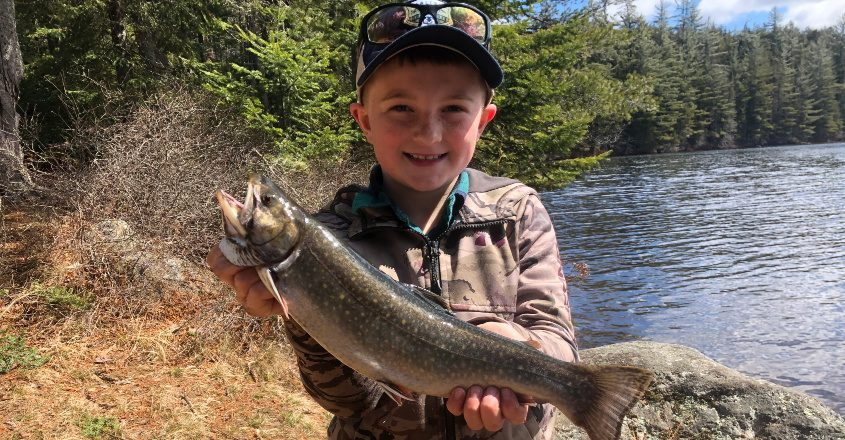 Ten-year-old Logan Hammons of Edinburg displays the 16-inch brook trout he caught while fishing with his father Doug.