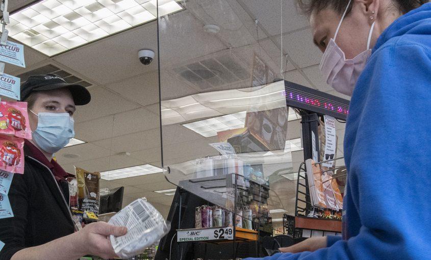 Stewart's employee Jessica Auryansen hands a customer a pack of free masks in Amsterdam last month