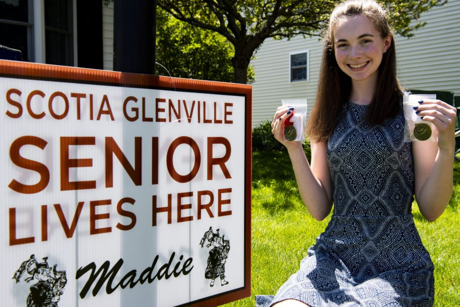 Scotia-Glenville senior Maddie Durant holds her scholastic and departmental medals in front of her home Friday, May 22, 2020.