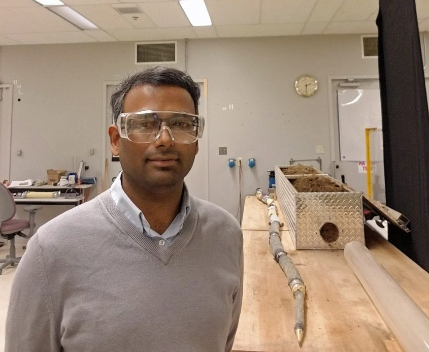 GE Research project leader Deepak Trivedi is shown in the lab with a prototype of an 8-foot robotic earthworm.