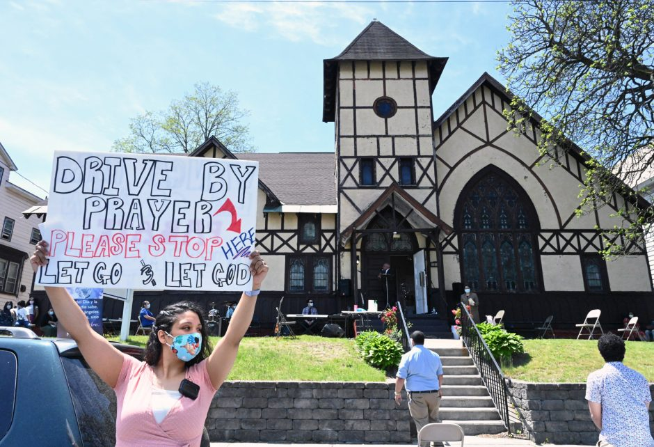 Erica Morillo holds a sign in front of Iglesia Pentecostal Dios Proveera Church in Schenectady on Sunday.