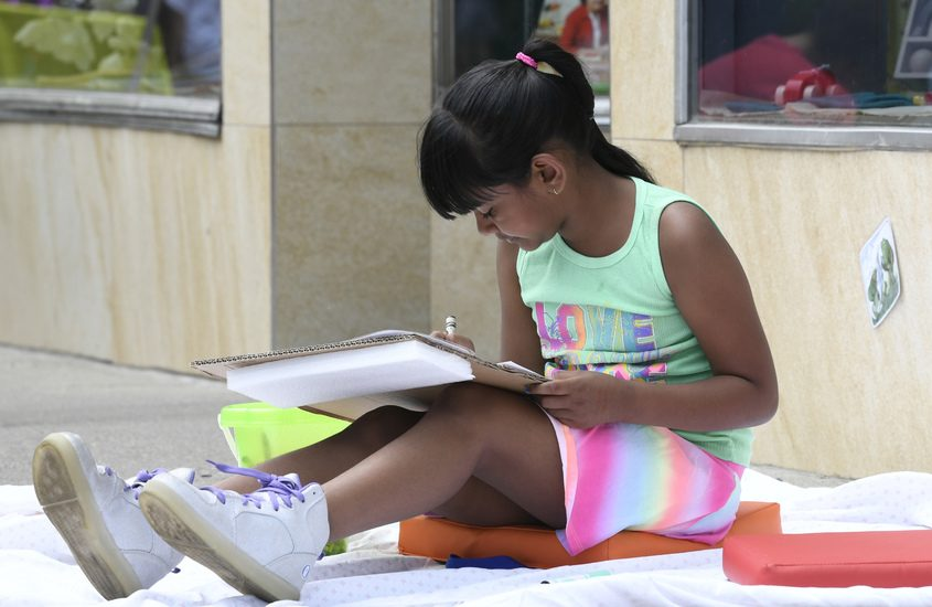 A girl draws in front of the Open Door Bookstore during the 2019 Schenectady Kids Arts Festival.