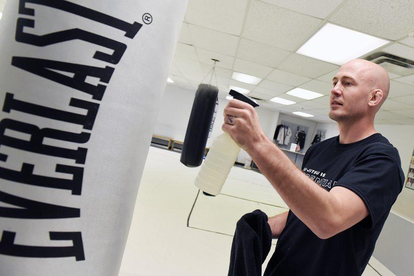 Eddie Fyvie sanitizes a heavy bag at his Malta jiu-jitsu academy Wedneday