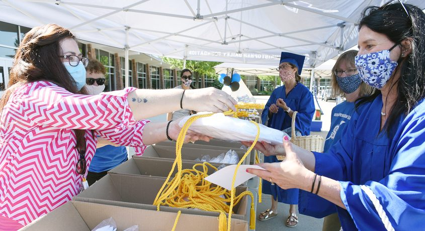 Volunteer and mother Lisa Maslak,of Saratoga Springs, gathers a seniors cap and gown at Saratoga Springs High School Wednesday