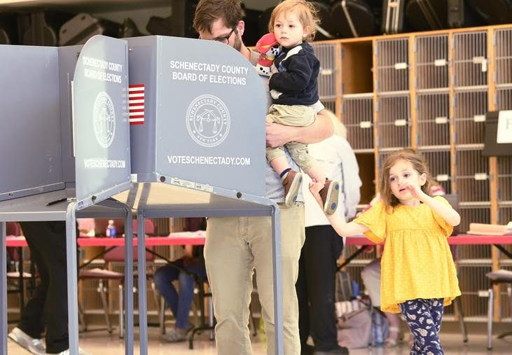 Sam Hayes of Niskayuna casts his vote for the school budget with his children at Niskayuna High School, May 21, 2019.