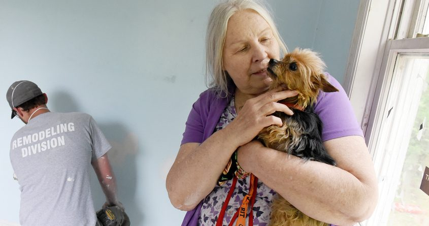 Linda Henle holds her dog, Chloe, after a downed tree from a tornado heavily damaged her home on Colebrook Road in Gansevoort.