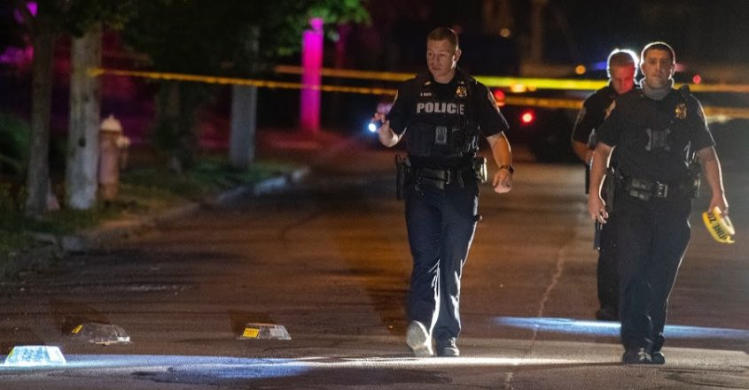 Schenetady police officers walk past shell casings on Broad Street Tuesday night